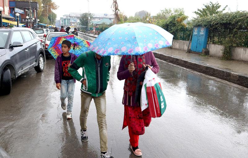 People use umbrellas as rains lash Srinagar on Sunday. —Excelsior/Shakeel
