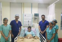 A team of doctors of SMVDNSH posing with a child after successfully performing open heart surgery.