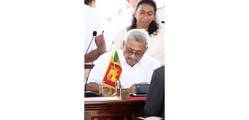 Sri Lanka's new President Gotabaya Rajapaksa signs documents during his swearing-in ceremony at the Ruwanwelisaya temple in Anuradhapura.