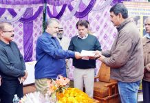 Principal Secy, Dr Asgar Samoon handing over insurance cheque to a farmer at Jammu.