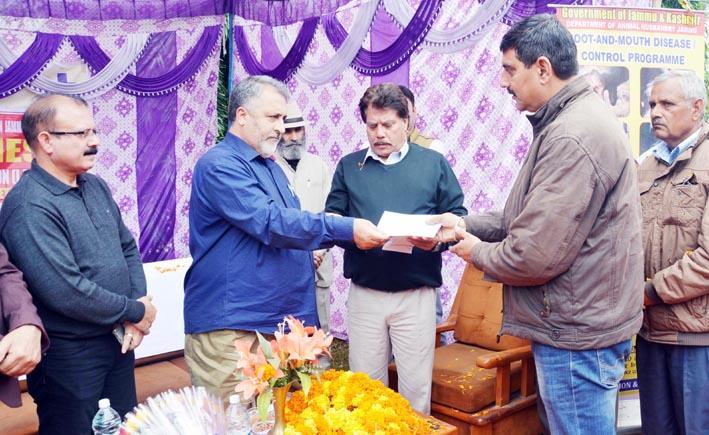 Principal Secy, Dr Asgar Samoon handing over insurance cheque to a farmer at Jammu.