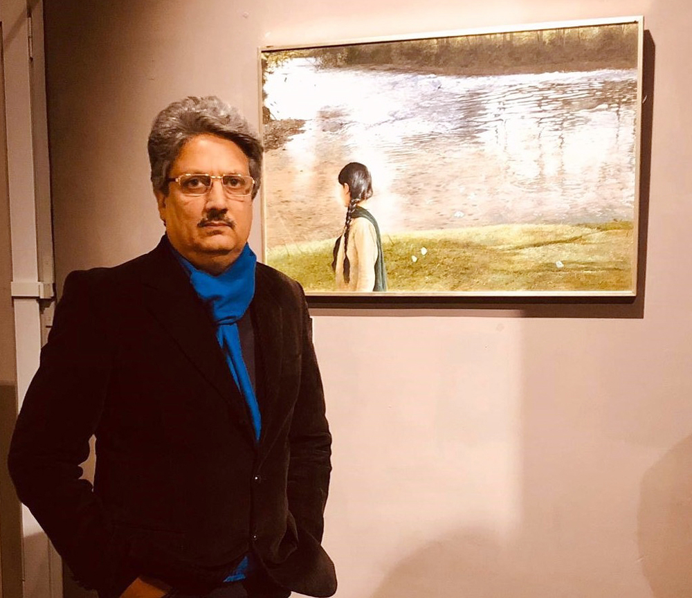 Suman Gupta posing with his painting work displayed on the wall behind.