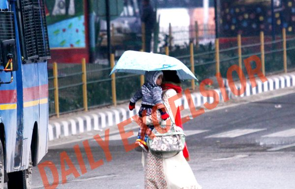 A woman along with her child, taking umbrella cover, moves on Jammu road during heavy rain on Thursday evening. -Excelsior/ Rakesh