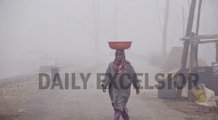 A woman walks amid dense fog in Srinagar on Tuesday. -Excelsior/Shakeel
