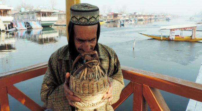 A boatman warms his face with 'Kangri' on the shore of Dal lake in Srinagar on Sunday. (UNI)