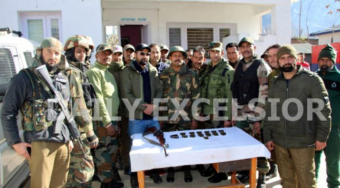 Security personnel pose with arms and ammunition recovered from militant in Kishtwar on Tuesday. -Excelsior/Tilak Raj