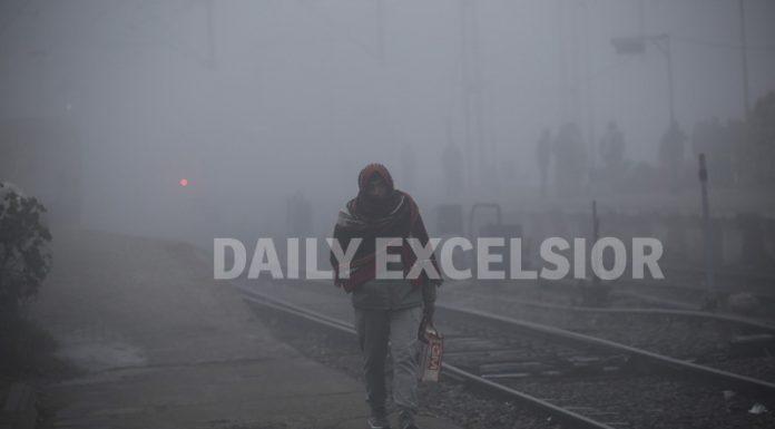 A passenger walks through dense fog at Jammu Railway Station on Monday morning. —Excelsior/Rakesh