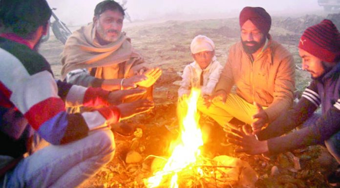 People warm themselves on a chilly morning in Jammu. —Excelsior/Rakesh