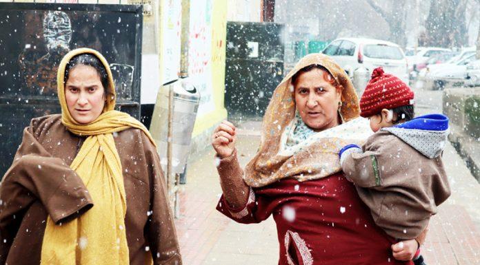 Women walk amid fresh snowfall in Srinagar on Friday. -Excelsior/Shakeel