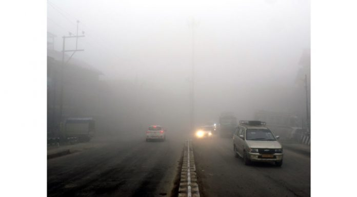 Vehicles plying amid dense fog in Srinagar on Saturday. (UNI)