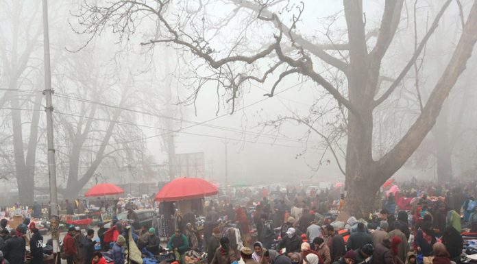 People purchase clothes and blankets amid dense fog and cold at Sunday market in Srinagar. — Excelsior/Shakeel