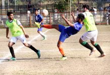Footballer kicking the ball in acrobatic style while his rivals make valiant efforts to get hold of the ball in Jammu on Sunday. -Excelsior/Rakesh