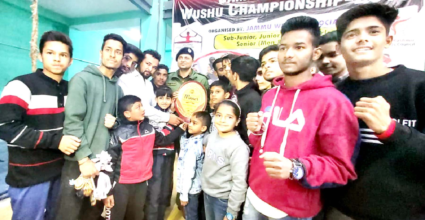 Champions posing along with chief guest Vinay Sharma, SP South during the concluding ceremony of District Wushu Championship in Jammu.