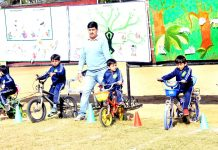 Children enjoy a ride on cycles during Annual Sports Day at Roots-the Montessori House in Jammu.