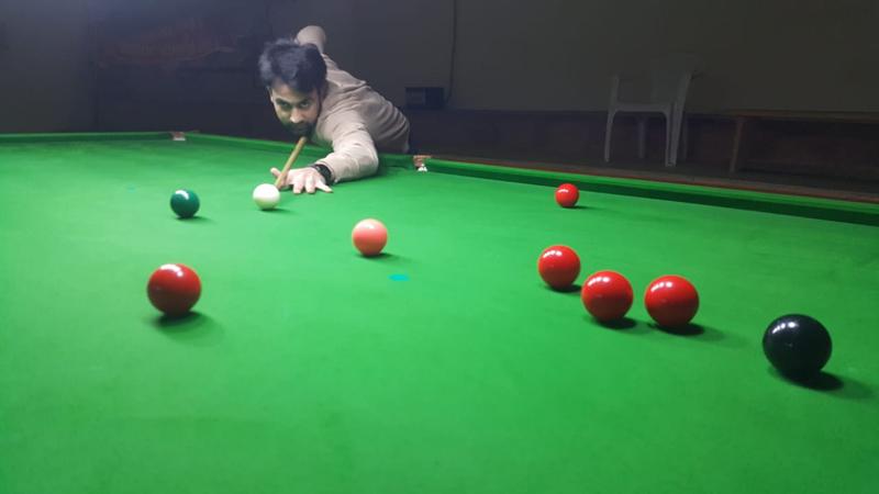 Cueist aiming at target at Billiards Hall, MA Stadium in Jammu.