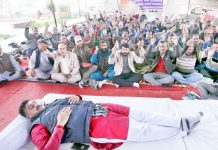 A Sarpanch observing fast at dharna venue while others protesting in Jammu on Sunday. -Excelsior/Rakesh