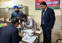 A doctor examining the eyes of a TBA member during an eye checkup camp in Jammu.