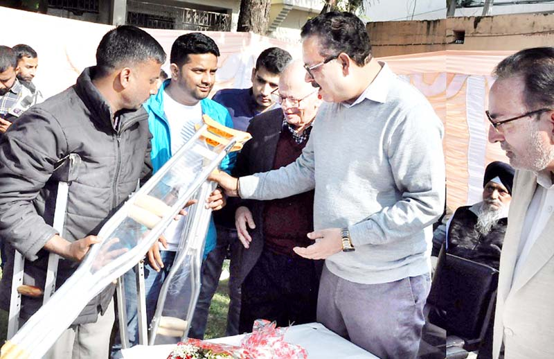 Principal Secretary Industries, Navin Choudhary distributing crutches to differently abled people in Jammu on Sunday.