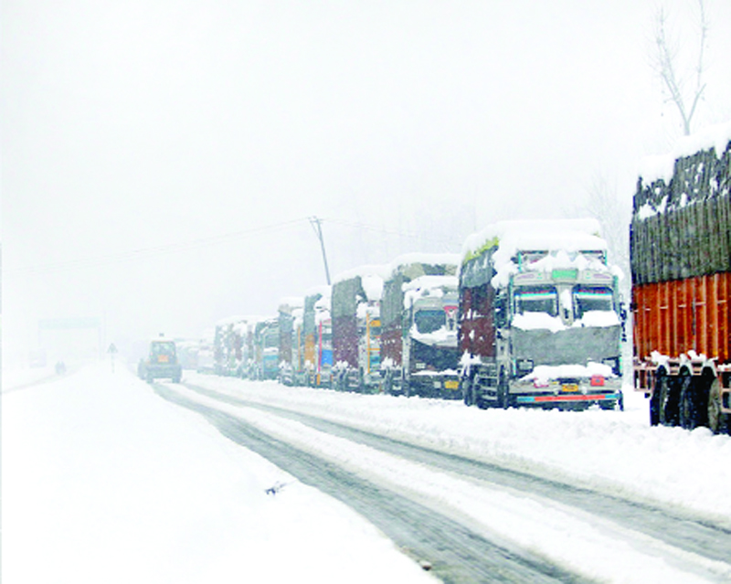 Trucks stranded amidst heavy snowfall at Anantnag in Kashmir on Friday.
