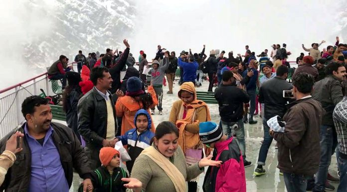 Mata Vaishno Devi pilgrims enjoy snowfall enroute the cave shrine on Tuesday. -Excelsior/Karandeep
