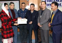 DPT J&K Naseer Ahmad Zargar along with others presenting certificate and prize to a winner of debate.
