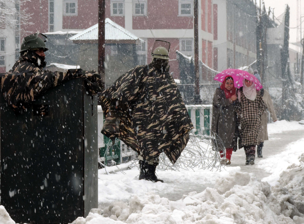 Girls sharing umbrella passing behind security forces, who are standing guard on Amira Kadal bridge despite snowfall which disrupted normal life in Valley on Wednesday. (UNI)