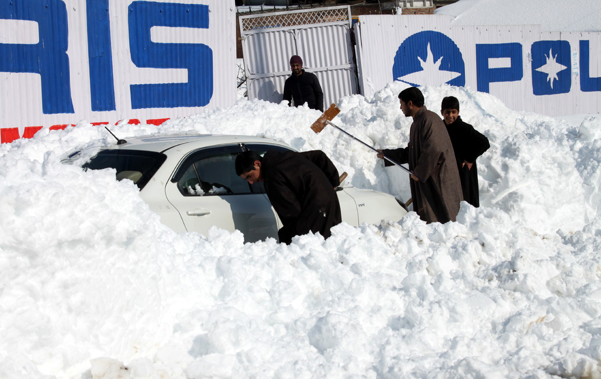 A car buried in snow being removed by people at Tangmarg in Kashmir. —Excelsior/Aabid Nabi