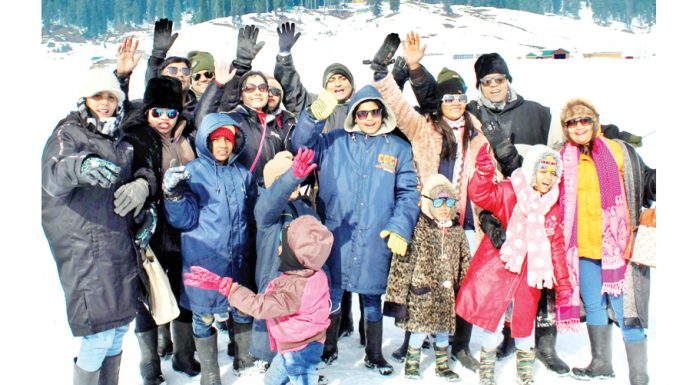 Tourists pose for photograph at Gulmarg. -Excelsior/Aabid Nabi