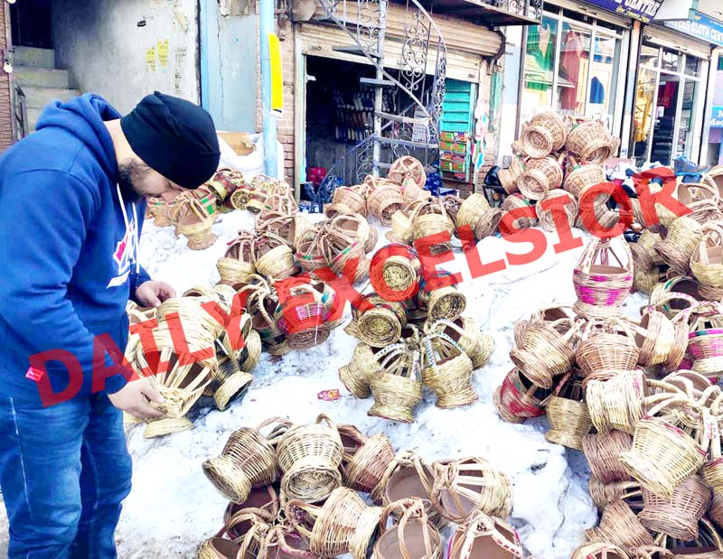 A man checking the quality of 'Kangri' (traditional fire pot) before buying it at Main Market in Shopian. —Excelsior/Younis Khaliq