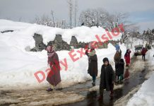 Women carry water pots on their heads on a snow covered road at a village in Budgam. — Excelsior/Shakeel