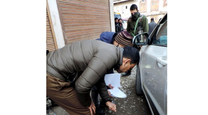 Security personnel collecting splinters for forensic experts at Kawdara in downtown Srinagar on Saturday. (UNI)