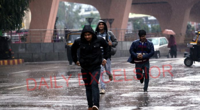 Amidst heavy rain, youth running for cover on a Jammu road on Monday. -Excelsior/Rakesh