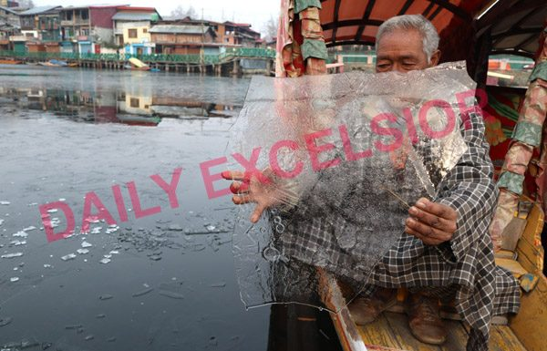 A boat man showing frozen Dal lake by lifting solid upper water layer in hand at Srinagar. —Excelsior/Shakeel