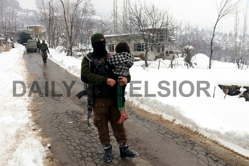 A JKP jawan rescue a Kashmiri child from an encounter site in Khrew, Pulwama in South Kashmir on Tuesday. -Excelsior/ Younis Khaliq