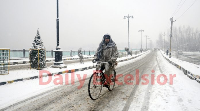A cyclist moves on a snow clad road in Srinagar on Sunday. — Excelsior / Shakeel