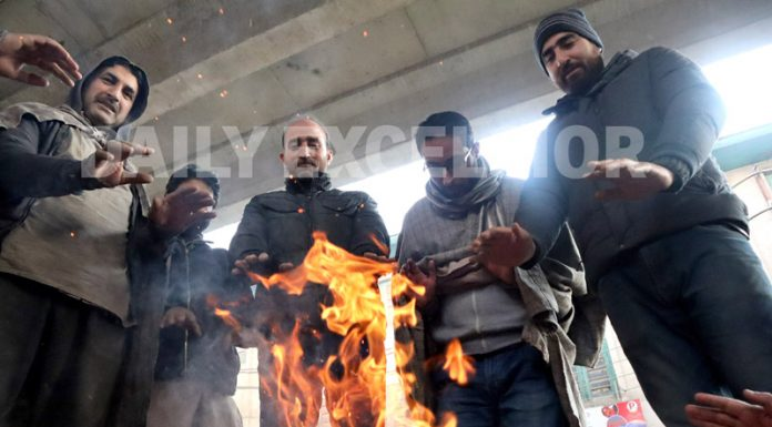 People warm themselves on a cold day in Srinagar. -Excelsior/Shakeel