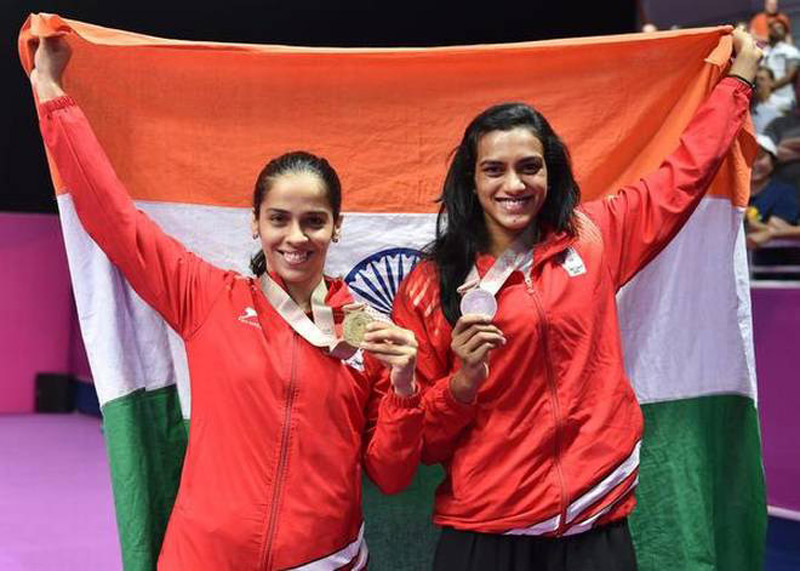 Saina Nehwal and PV Sindhu holding Indian flag after entering second round of Malaysian Masters in Kuala Lumpur.