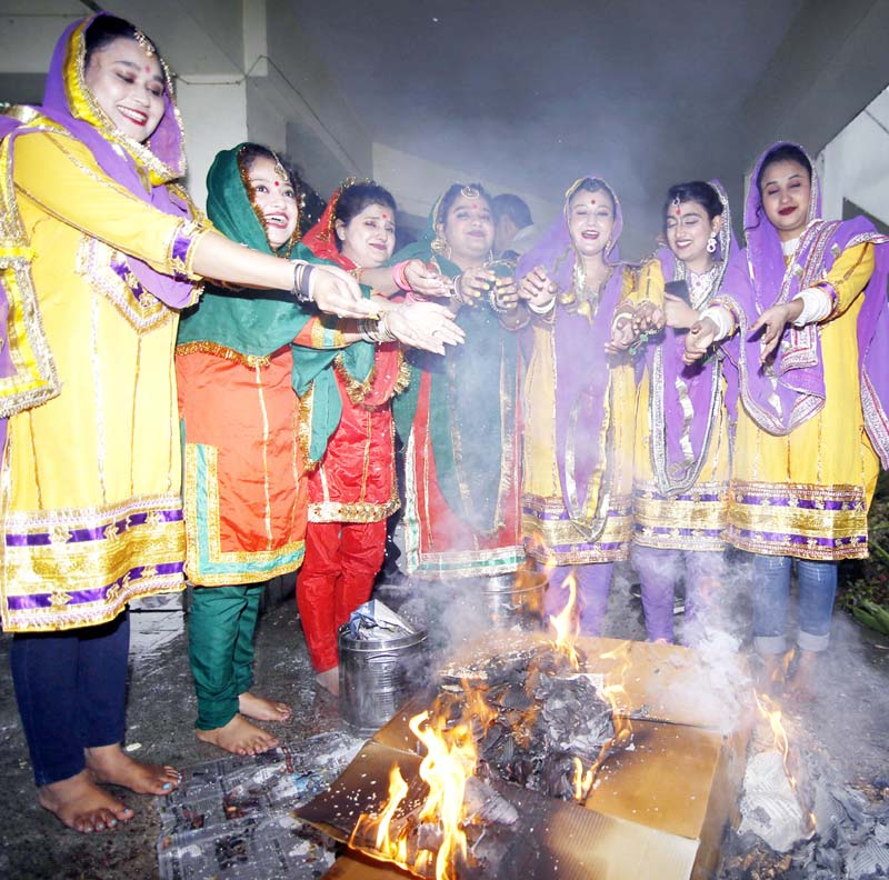 Group of women offering mixture of peanuts and sugarcane products to fire as a ritual on the occasion of Lohri on Monday. -Excelsior/Rakesh