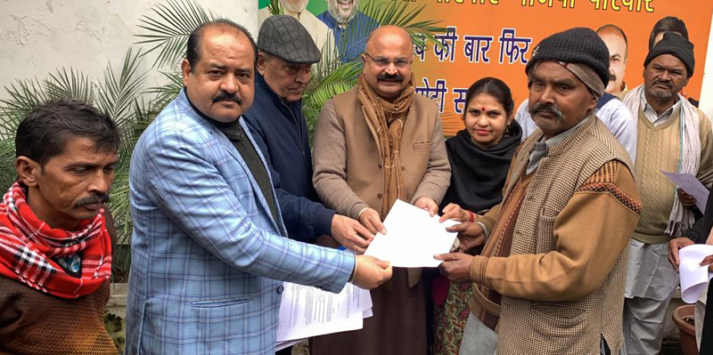BJP general secretary, Yudhvir Sethi distributing PMAY letters to beneficiaries at Jammu on Thursday.
