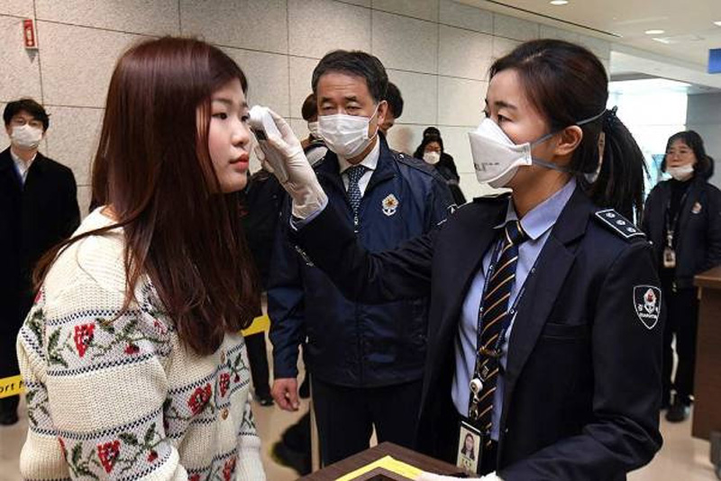 A quarantine officer, right, checks the body temperature of a passenger at the Incheon International Airport in Incheon, South Korea.