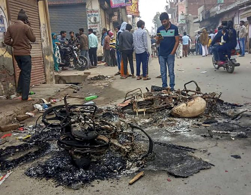Passersby look at the charred remains of vehicles which were set ablaze by rioters during clashes at Mustafabad area of East Delhi on Wednesday.
