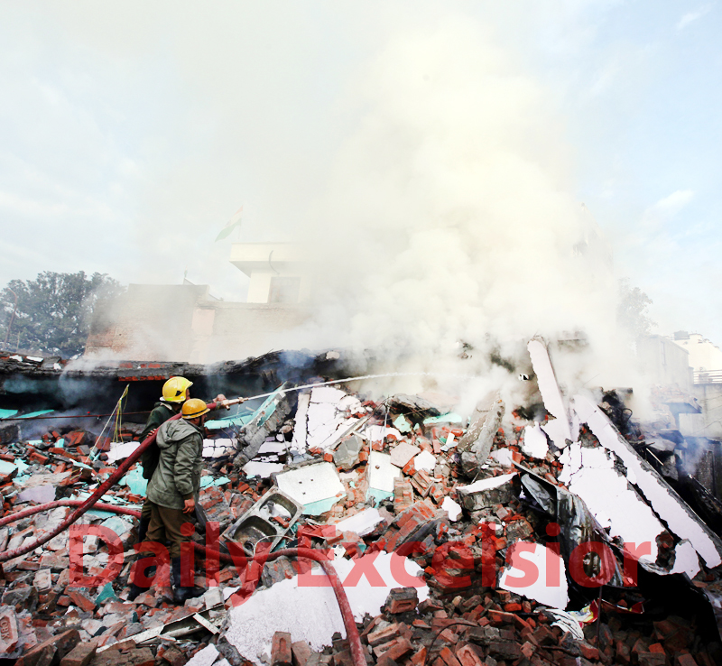Fire fighters dousing flames coming out from the debris of a building at Talab Tillo in Jammu on Wednesday. —Excelsior/Rakesh