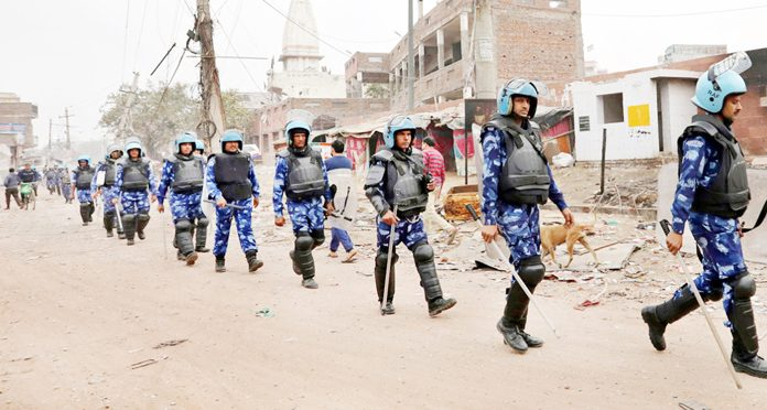 Members of Rapid Action Force patrol a road in a riot affected area in New Delhi on Friday.