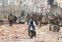 Men ride a motorcycle past security forces patrolling a street in a riot affected area in New Delhi on Wednesday.