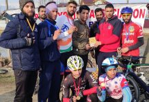 Winners of the Budgam Cycling Championship posing with chief guest at Budgam.