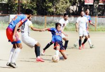 Players in action during a match of J&K Football championship in Jammu on Sunday.