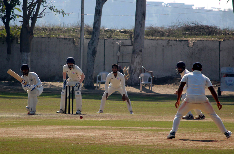Batsman executing a sweep while fielders watch during a match between J&K and Haryana at GGM Sciecne College Hostel ground in Jammu. —Excelsior/Rakesh