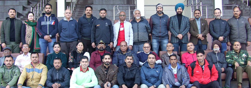 Selected veteran athletics team of J&K poses with officials of J&K Sports Council at MA Stadium, Jammu.