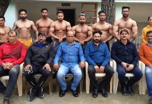 Nine member team of J&K Body Building posing for a group photograph along with dignitaries in Jammu.
