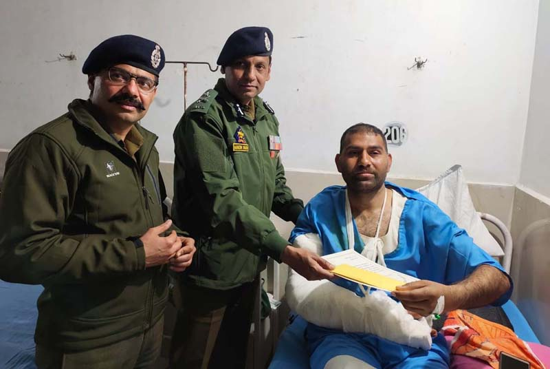 IGP Jammu Zone Mukesh Singh presenting Commendation Certificate Class-I alongwith cash prize to injured cop at GMC Jammu on Saturday. SSP Jammu Tejinder Singh is also seen in the picture.